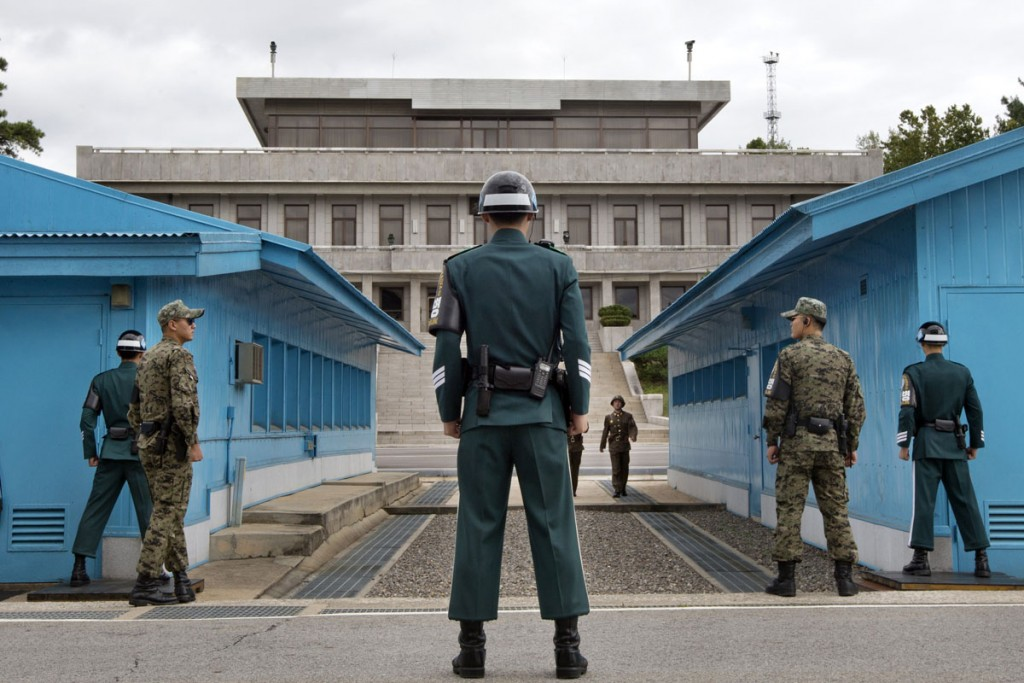 South Korean soldiers look towards the North Korean side as a North Korean solder approaches the U.N. truce village building that sits on the border of the Demilitarized Zone (DMZ), the military border separating the two Koreas, during the visit of U.S. Secretary of Defense Chuck Hagel, in Panmunjom, South Korea September 30, 2013. Hagel toured the Korean DMZ on Monday, at times under the watchful eye of North Korean soldiers, and said the Pentagon had no plan to reduce its 28,500-member force in the South despite budget constraints. REUTERS/Jacquelyn Martin/Pool (SOUTH KOREA - Tags: POLITICS MILITARY) - RTR3FFOW